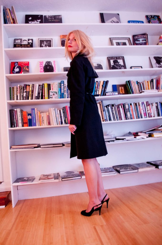 Trench coat with bookcase in the background