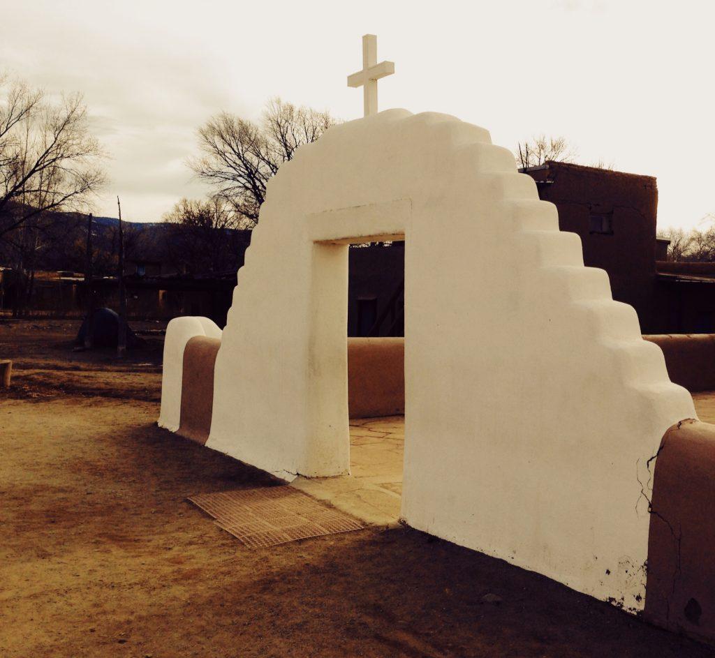 Desert white cross entrance - Taos Pueblo