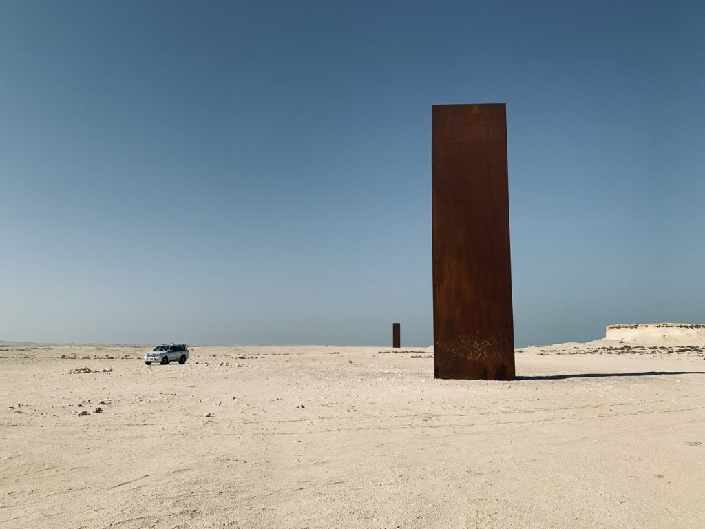 Qatar horizon with large vertical steel structure by Richard Serra.