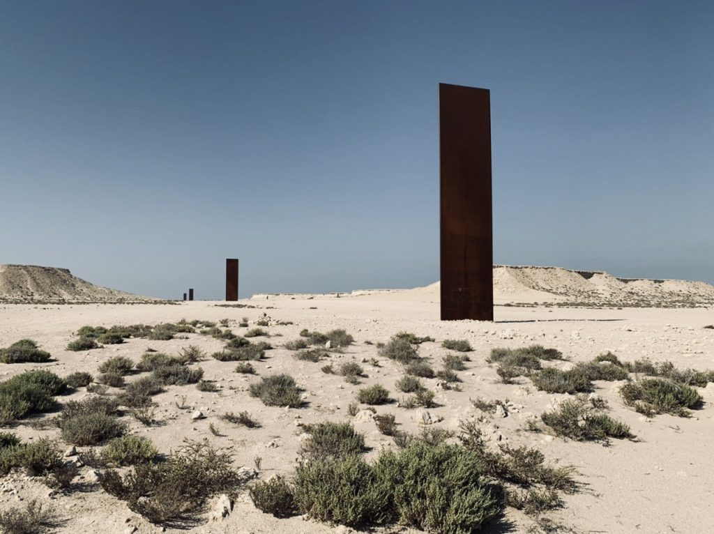Four large amber colored vertical steel Sculptures by Richard Serra  in the desert of Qatar
