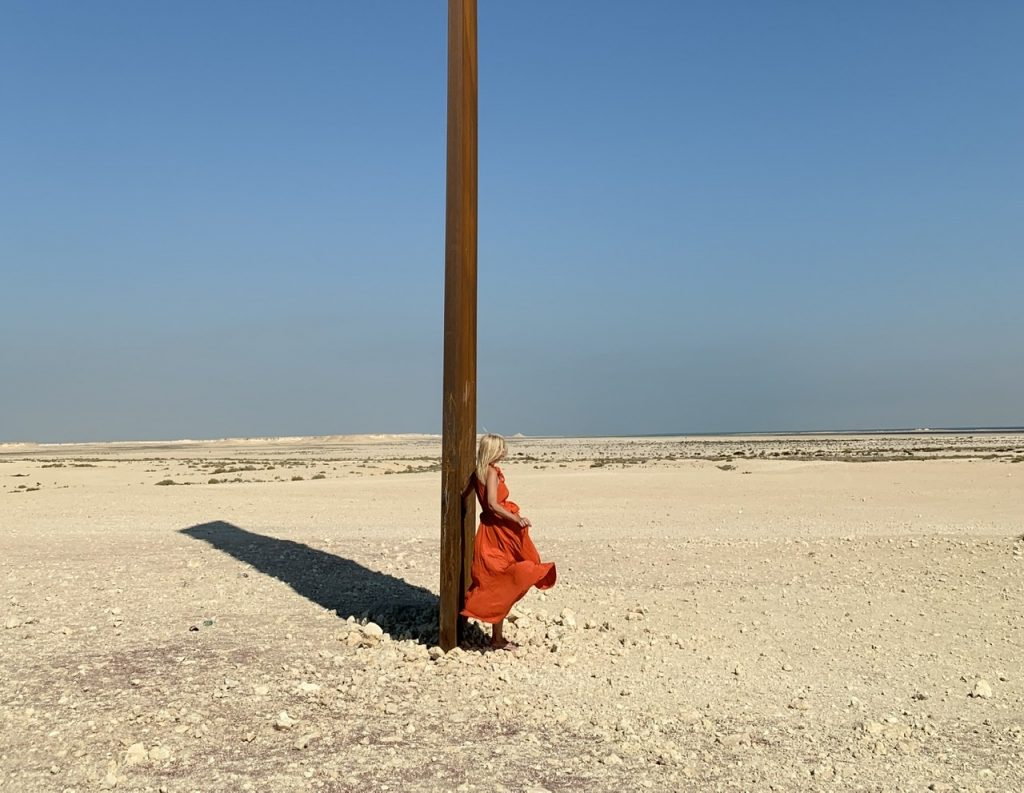 Tijana in burnt orange Kalita dress leaning against East-West/West-East in Qatar.  Kalita dress