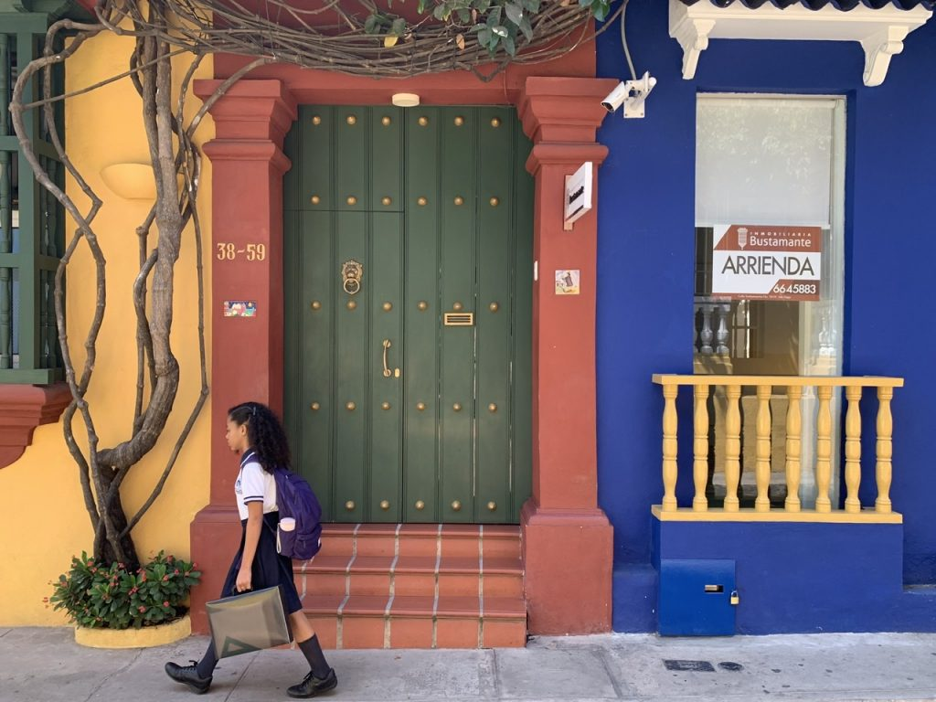 A young girl walks to school in front of bright yellow, brick, and blue colored walls in Cartagena