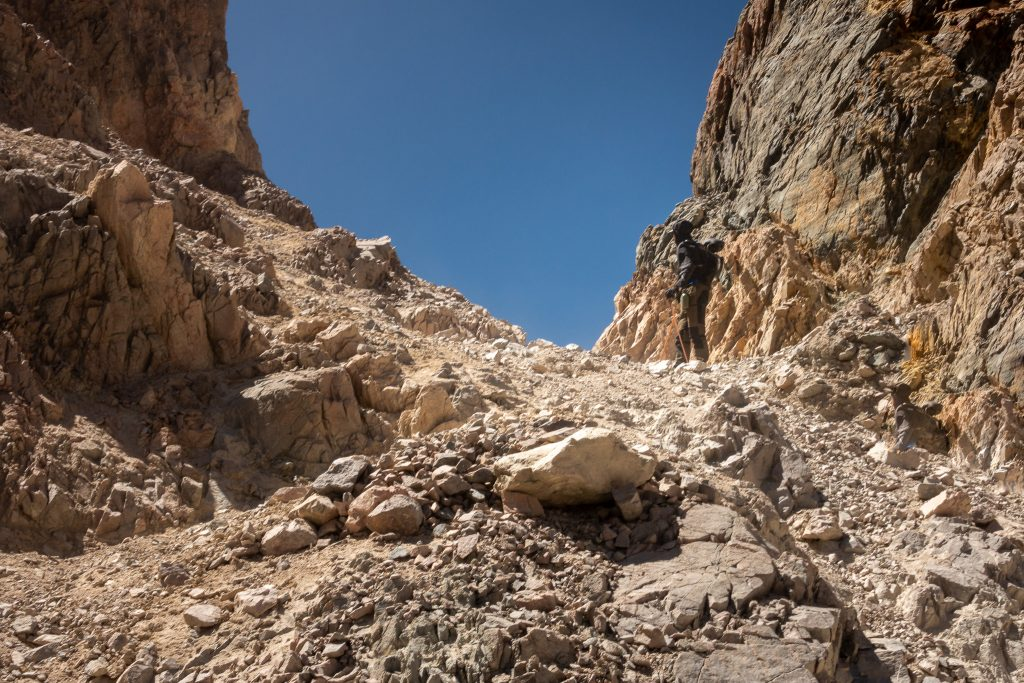 A hiker going through the crumbling rocks found on the Piuquenes Pass trail
