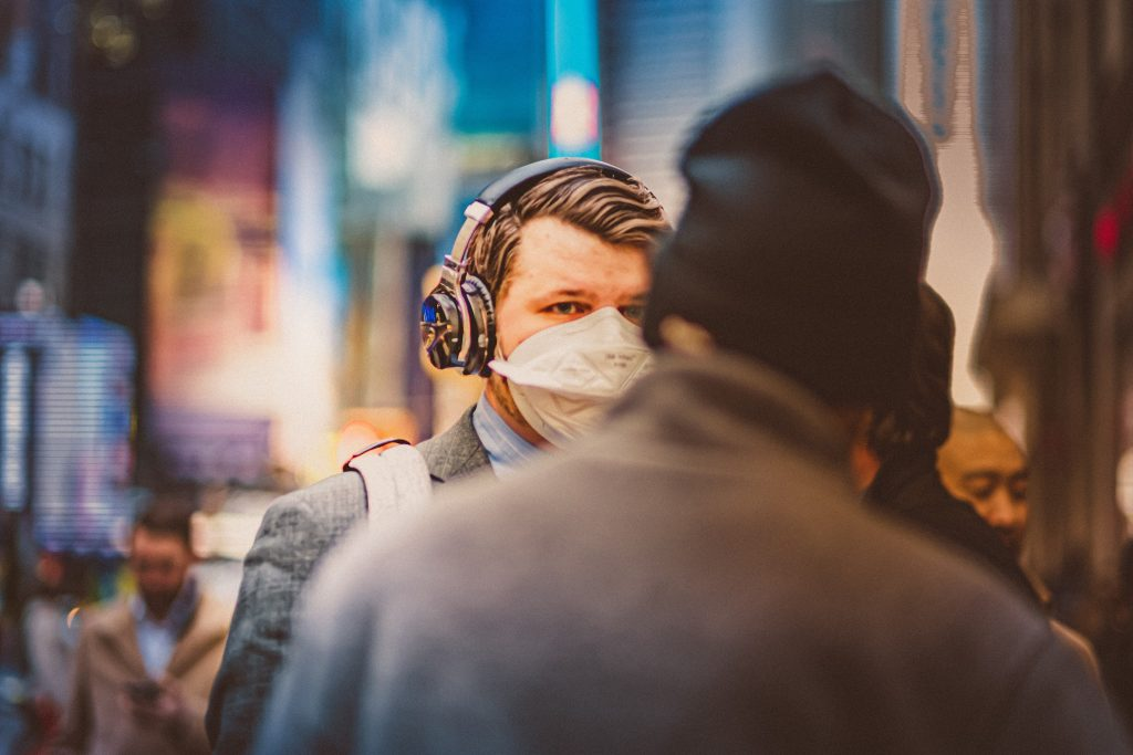 A business man walks down the street wearing a mask, Photo by Petar Pavlov.