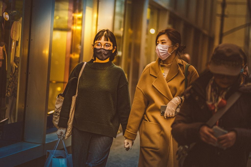 Two women walk down the street wearing masks, Photo by Petar Pavlov.