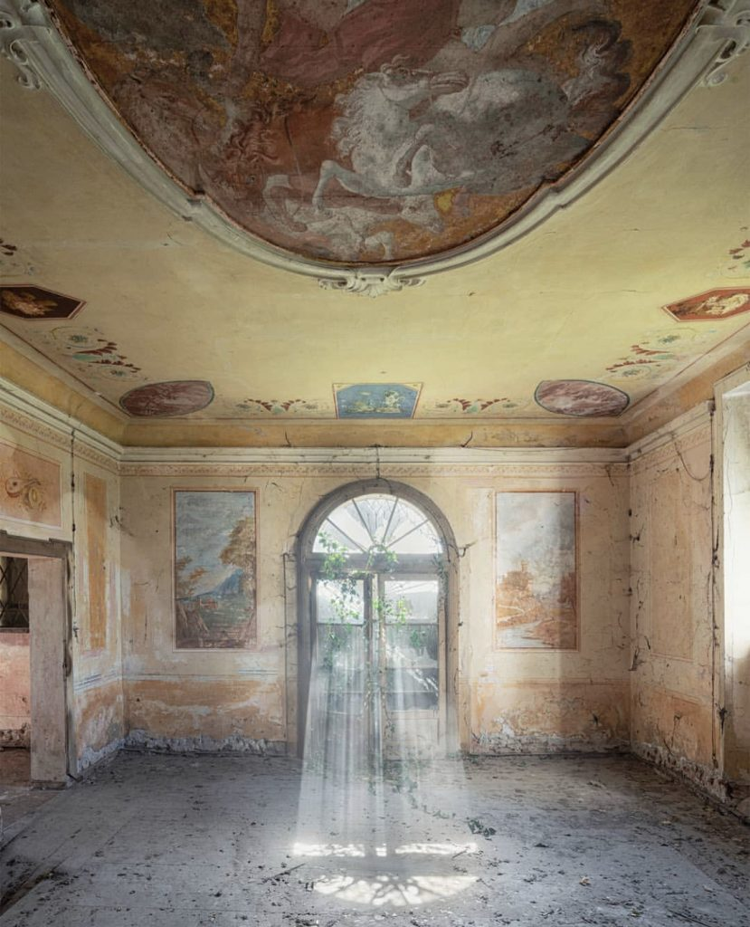 Arcana Imperii by Nicola Bertellotti. Light floods an abandoned room with sand colored walls.