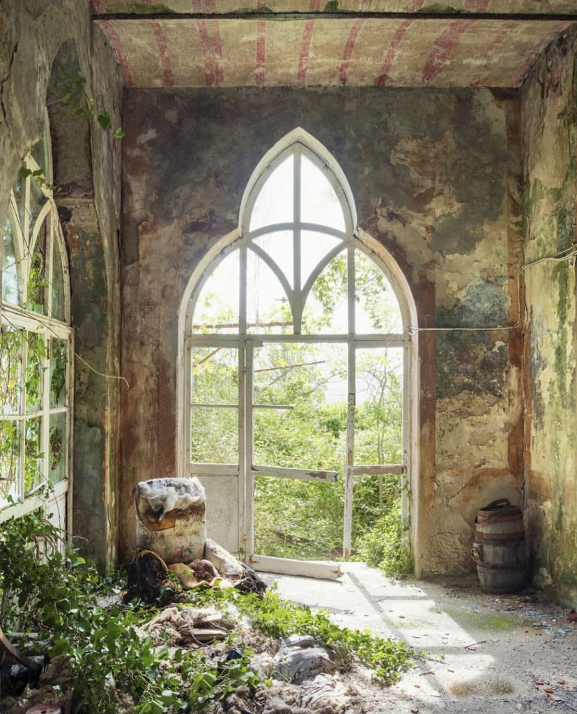 Il posto delle fragole by Nicola Bertellotti. A decaying window frame is slowly taken back by nature.