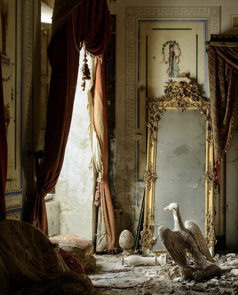 L'Horizon Chimérique by Nicola Bertellotti. Light pours through decaying curtains onto a dusty but intricate gold mirror and bust of an eagle.