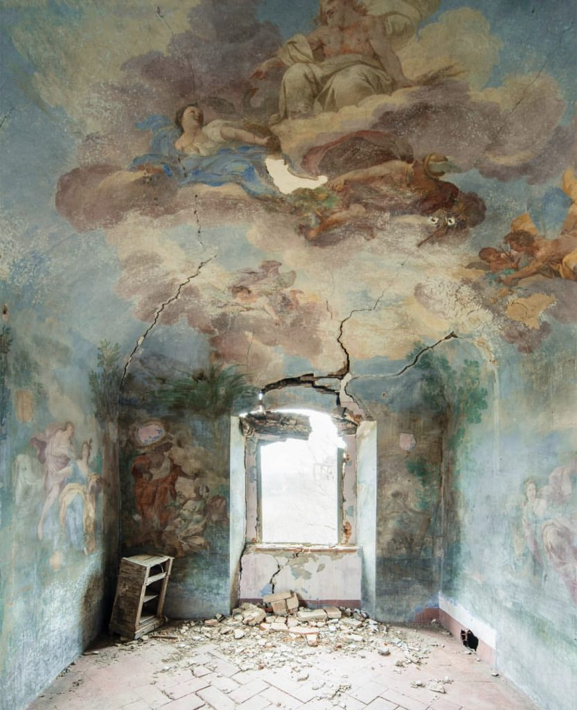 Resilient Sky by Nicola Bertellotti. A large crack comes from the window of a decaying room covered in forgotten murals of angels and religious figures.