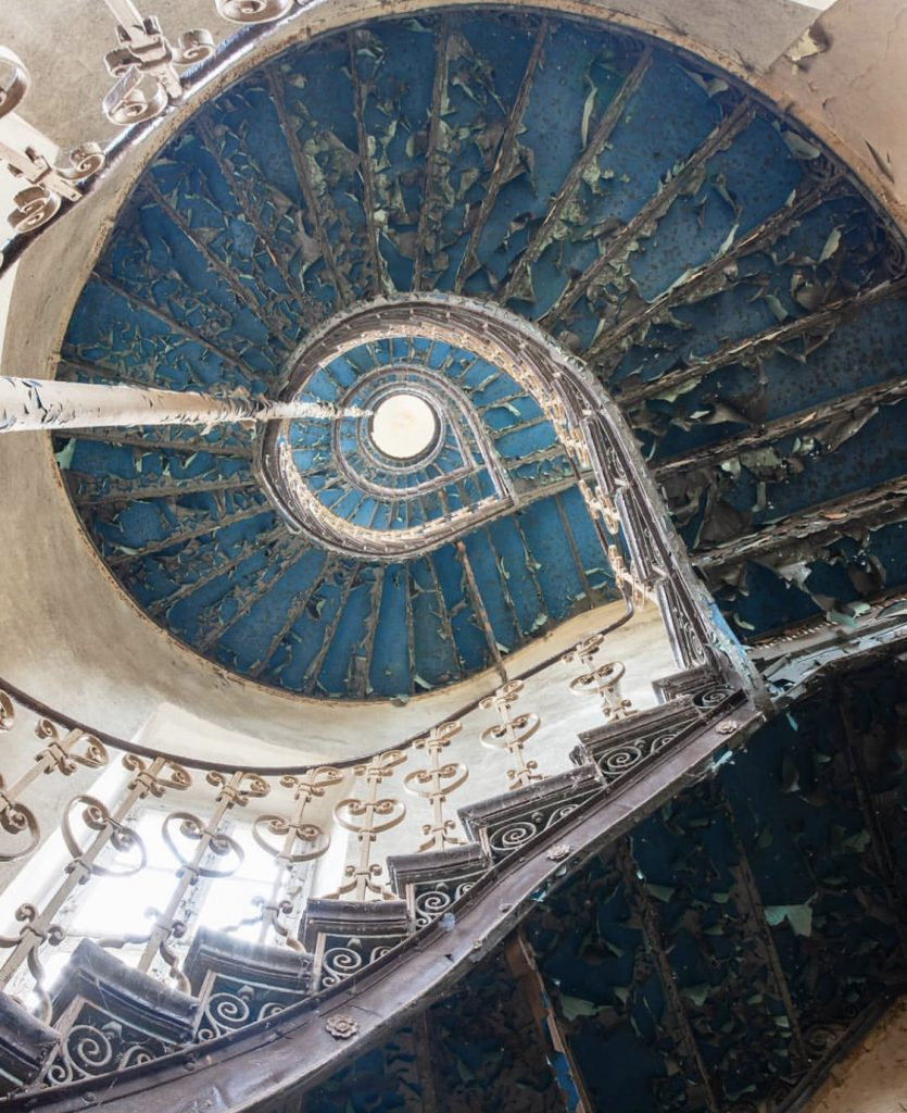 Le Grand Bleu by Nicola Bertellotti. Looking up through the swirl of a peeling blue staircase into the light of the ceiling.