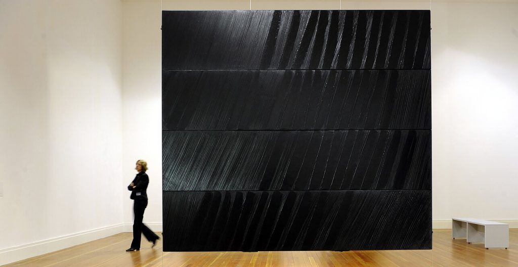 A woman walks past Pierre Soulages work in a gallery