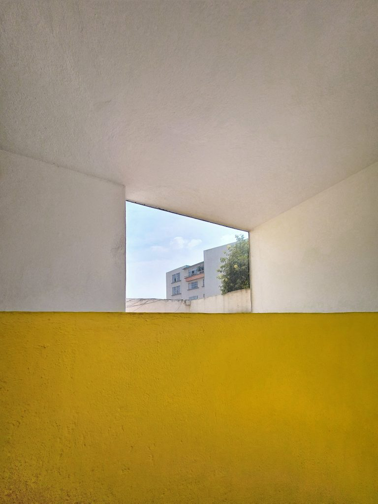Framing the environment with architecture. A yellow wall meets the outside.