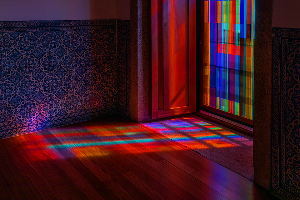 Light pours through the colored glass window installation and paints the floor with vibrant hues at the STRATA Exhibition at the Fundação Eugénio de Almeida Portugal.